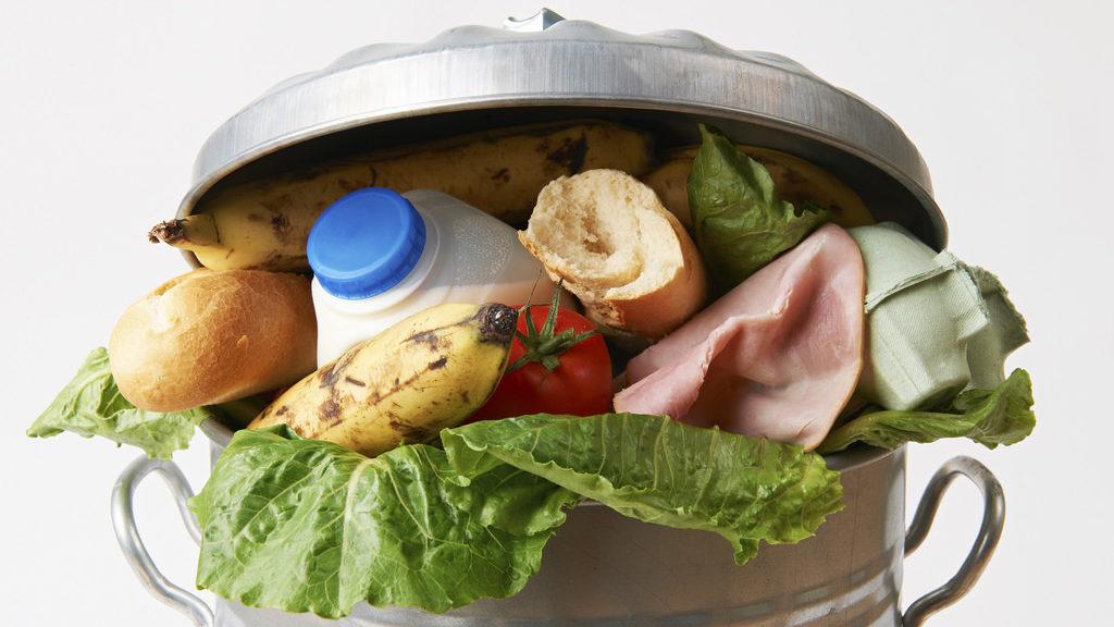 Aliments frescos al cubell d'escombraries per il·lustrar els residus.